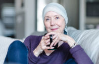 woman with cancer at home sipping tea
