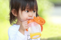 child drinking water from sippy cup