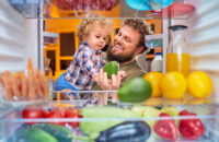 Man and son find healthy snack in fridge