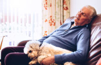 Elderly man takes nap in afternoon with his dog