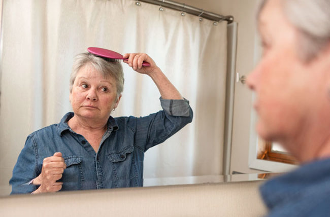 woman with grey hair looking in mirror