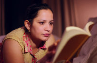 woman reading a book at night to promote sleepiness