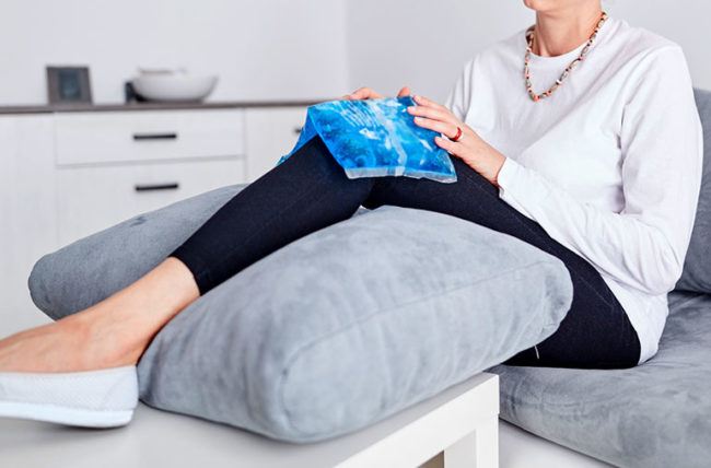 Woman icing and elevating her hurting knee