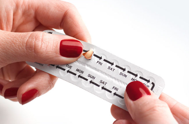 woman take birth control pill from packet