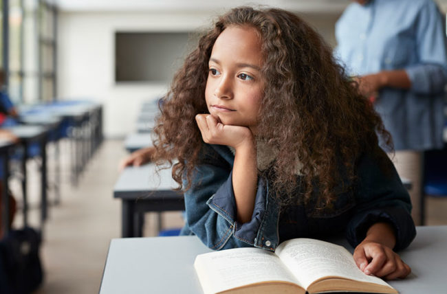 Adolescent girl disaffected holding book in class