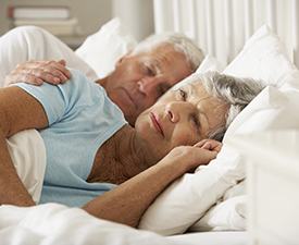 Senior Woman Having Difficulty In Sleeping In Bed With Husband