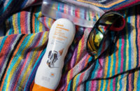 sunscreen water and sunglasses on beach blanket
