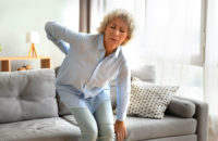 woman getting up from couch with back pain