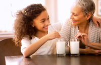 Grandmother and granddaughter enjoying glasses of milk or soy milk