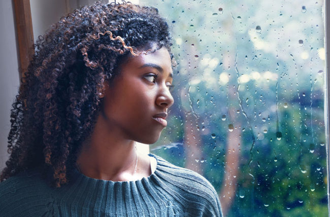woman looking out rainy window