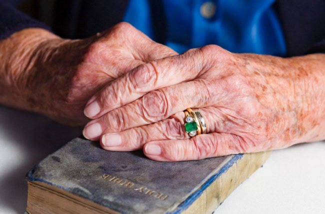 woman's hands with age spots holding bible