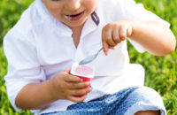 child sitting in grass eating yogurt