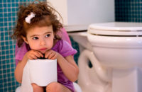 sad little girl with UTI sitting in bathroom