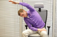 man performing yoga stretch at work