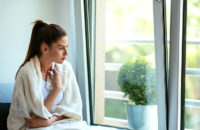 woman with sore throat sitting by open window