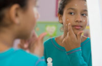 girl applying acne medication to face