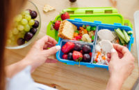 woman packing healthy lunch for her student athlete