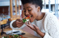 young woman eating vegetable pizza