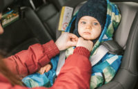 infant with puffy coat in getting put in care seat