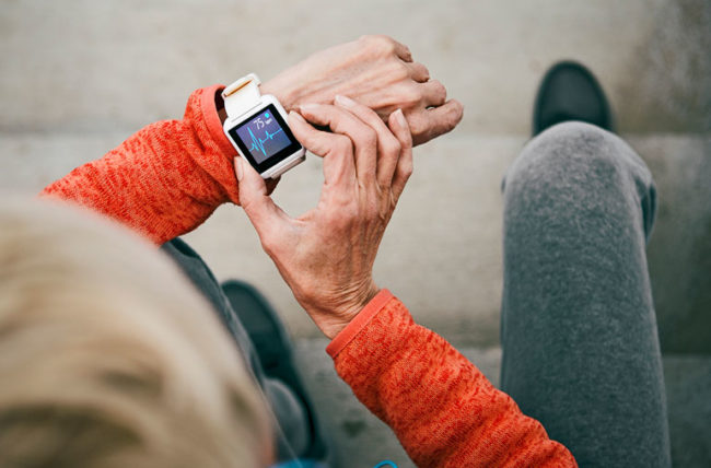 elderly woman checking her heart rate on a smart watch while exercising