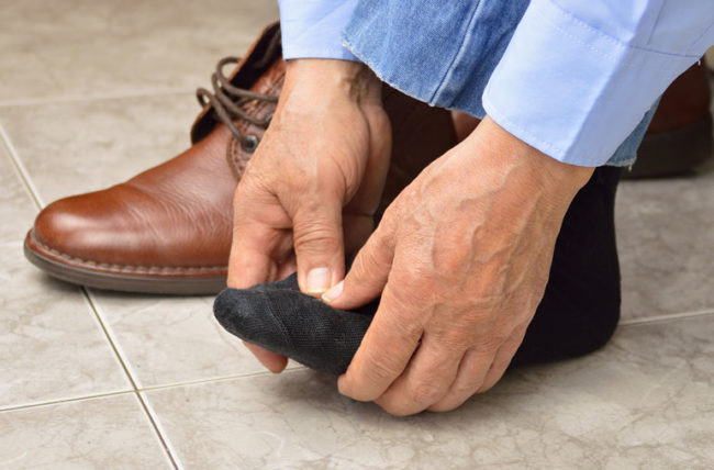 man massaging feet hurting from tight shoes