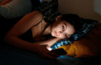 woman using smartphone in bed at night