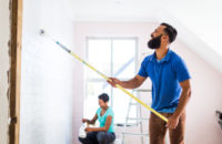 man and woman painting walls inside home