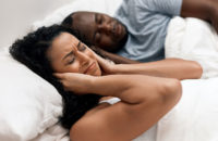 woman covering ears while husband snores in bed