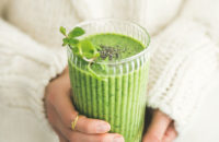 woman holding matcha smoothie