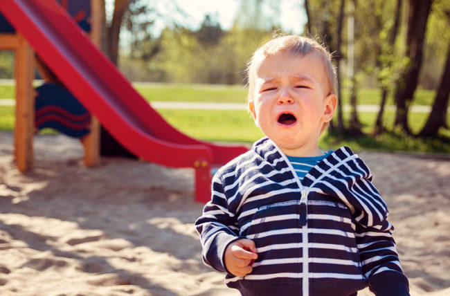 hurt little boy crying on playground