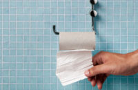 Hand in bathroom grabbing last of toilet paper