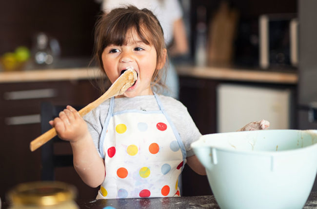 Girl eating cookie dough while cooking with mom