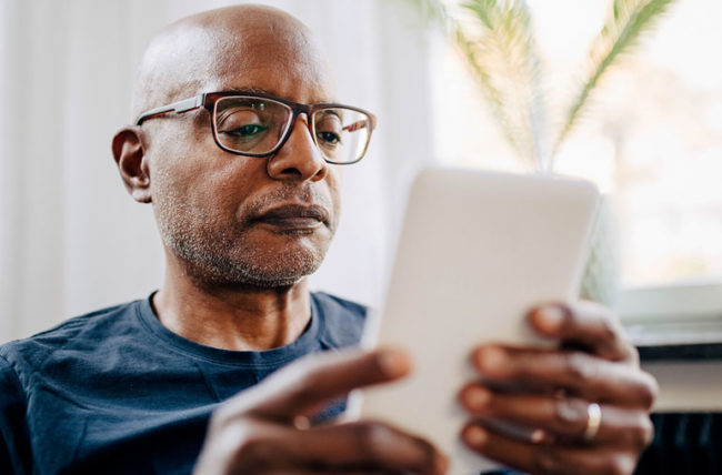 elderly man with glasses reading on iPad