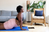 woman doing cobra yoga pose in her living room