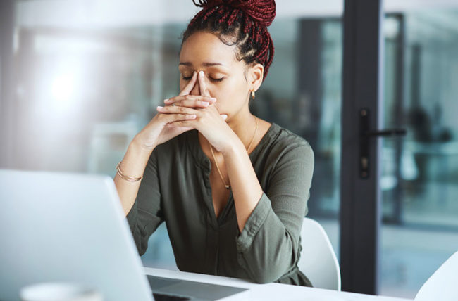 woman taking a deep breath at work to relieve stress