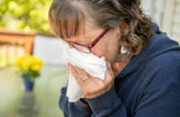 woman sneezing because of allergies