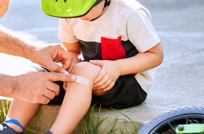 dad applied bandaid to child's knee