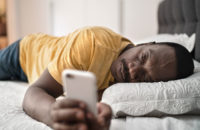 older man sick on bed with phone in hand