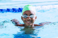 boy swimming in pool with goggles