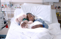 child hugging stuffed bear in hospital bed