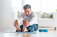 elderly man stretching out and lifting weights