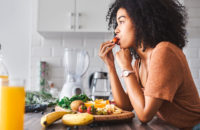 woman eating fruit in kitchen