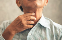 elderly man touching throat