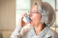 elderly woman using inhaler for asthma attack