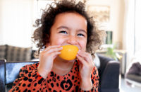 child eating orange