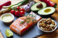 Foods on mediterranean diet, high in healthy fats such as Salmon, olive oil, nuts and avocados with vegetables and herbs.
