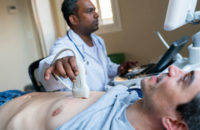 man undergoing echocardiogram with technician