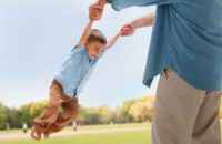 Father swinging child by arms