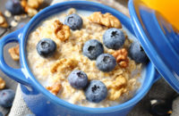 Bowl of oatmeal, blueberries and walnuts in a blue crock