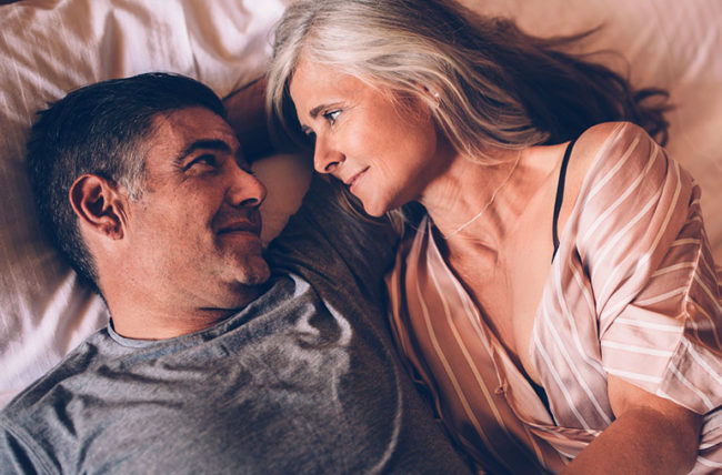 Romantic elderly couple relaxing together and lying down in bed